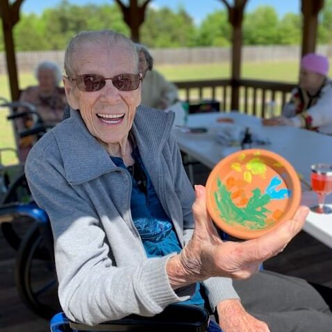 Assisted Living Activities Man holding up painted bowl and smiling